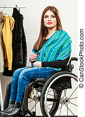 Invalid girl on wheelchair choosing clothes in wardrobe -...