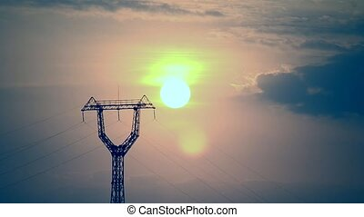 Time lapse of sunrise with transmission tower at dawn with...