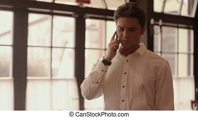 A man in a white shirt on the phone