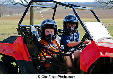 Boy and girl on dune buggy - Happy boy and girl riding a...
