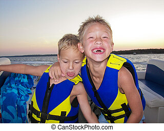Two adorable boys on a lake at sunset - Young boys in life...