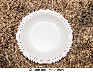 empty plate on the background of burlap.