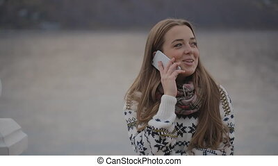 The young woman is talking on the mobile phone smiling and...
