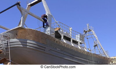 Welder working on new ship - On a sunny day welder is...