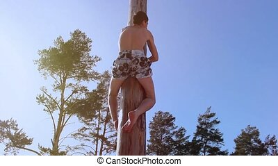 a man climbs a pole on holiday carnival - a man fun climbs a...