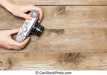 woman's hands holding a retro camera, flat lay