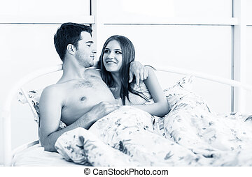 Loving couple in bed. Beautiful young loving couple lying in...