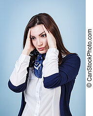 Young beautiful woman with headache on the blue background