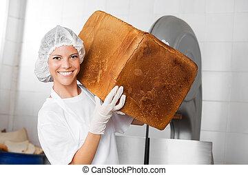 Smiling Female Baker Carrying Big Bread Loaf - Portrait of...