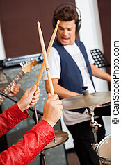Womans Hand Holding Drumsticks In Recording Studio - Cropped...