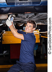 Happy Mechanic Working Underneath Lifted Car - Portrait of...