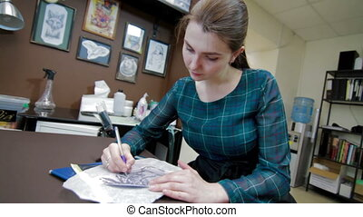 Female tattoo artist drawing tattoo sketch - tattoo artist...