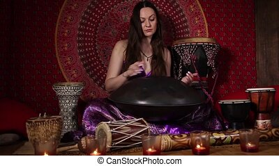 Woman playing hand pan indoors - Dolly video shot of a woman...