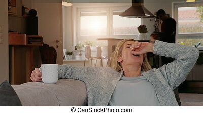 Attractive woman taking a break at home relaxing on the sofa...