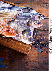Wooden box of ice filled with assorted fresh fish