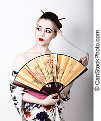 beautiful girl dressed as a geisha, she holds a chinese fan. Geisha makeup and hair dressed in a kimono. The concept of traditional Japanese values