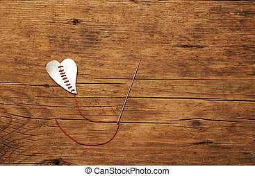 broken heart stitched with red thread on a wooden table.