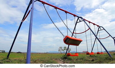 Empty Swings on Outdoor Playground - Orange chain swings on...
