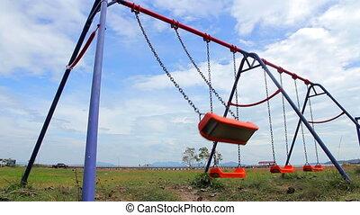 Empty Swings on Outdoor Playground - Orange chain swings on...