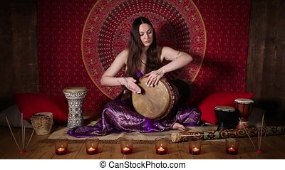Woman playing the drum indoors - Young Caucasian woman...