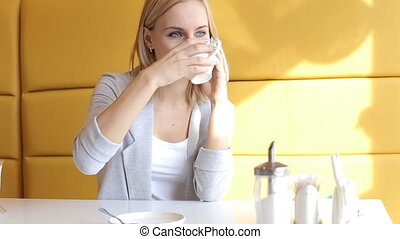 The girl stir and drink tea and speaks by phone in cafe.