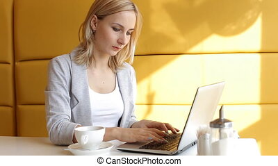 Young woman working on laptop in cafe