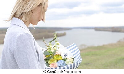 Beauty happy girl with curly blond hair smelling wild flowers and smiling.