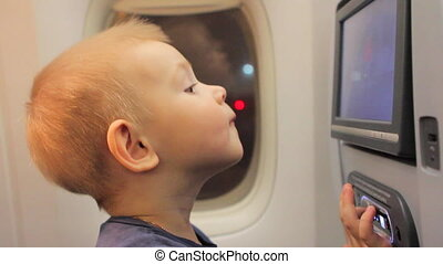 Boy Watching Cartoons on the Screen in Plane Seat