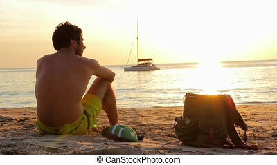 Man with Backpack Sitting on the Beach - Young man is...