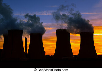Silhouette of power plant at sunset