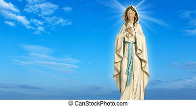 Statue of the Virgin Mary against blue sky - Statue of the...