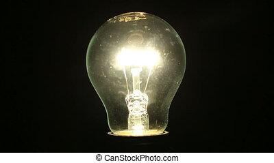 Light bulb illuminates a dark room