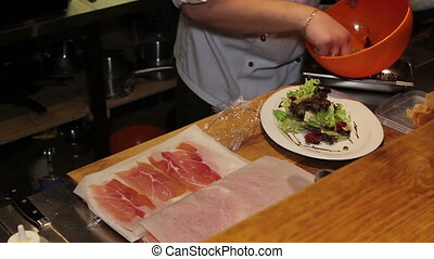 chef decorate salad with jamon in the restaurant - chef...