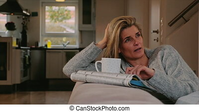 Thoughtful middle-aged woman sitting daydreaming on a...
