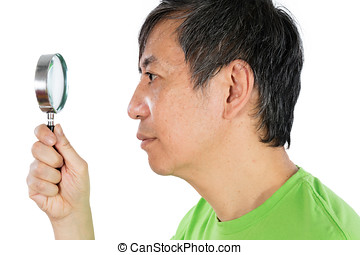 Asian Chinese Man Looking through a Magnifying Glass in...