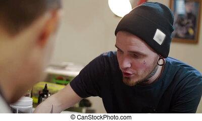 tattooist advises the client at the studio - tattooist...