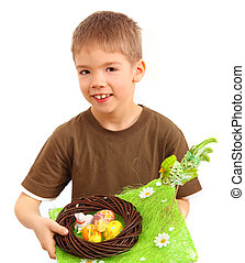 boy and easter nest full of colorful eggs
