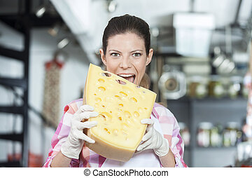 Young Saleswoman Biting Cheese In Store