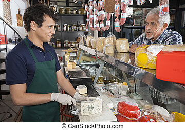 Man Talking With Salesman Slicing Cheese In Shop - Senior...