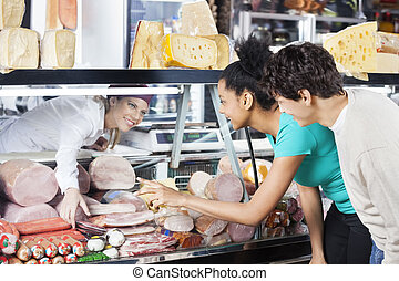 Couple Selecting Product From Display Cabinet While...