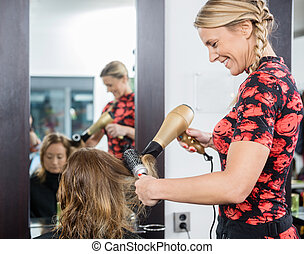 Hairdresser Styling Customer's Hair With Blow Dryer And...