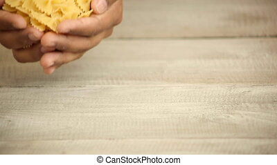 Hands pouring pasta onto wood