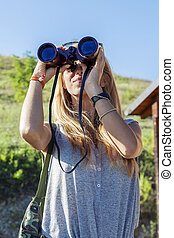 pretty girl with binoculars looking at the horizon