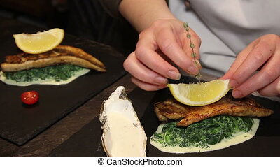 chef preparing fish with spinach and capers sauce - tasty...