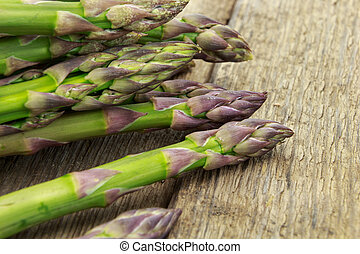Bunch of asparagus tips closeup on wooden surface