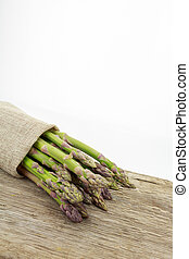 Bunch of asparagus tied with raffia cloth on wooden surface...