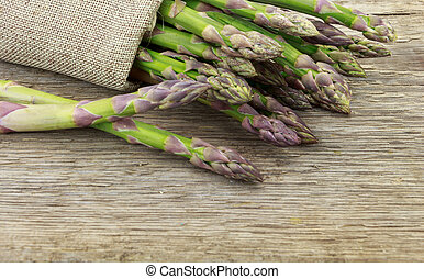 Bunch of asparagus tied with raffia cloth on wooden surface