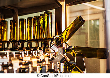 Unlabeled glass bottles in bottling machine at modern winery...