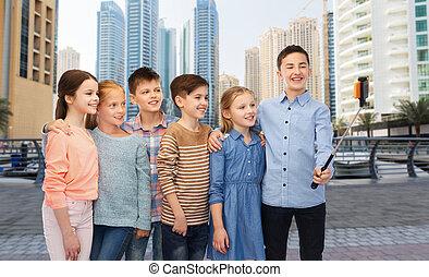 feliz, niños, con, smartphone, y, selfie, palo,