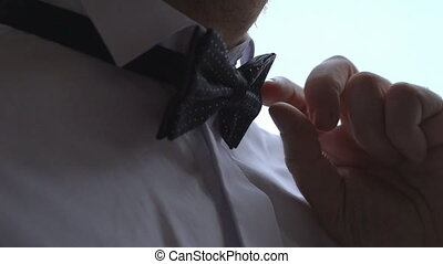 man corrects businessman bow tie close up shot